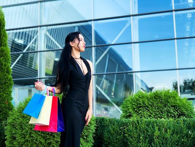 Einkaufstag. frau, die farbige taschen nahe ihrem shooping mall in schwarzem freitag-feiertag hält