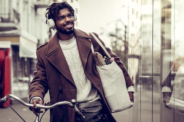 Einkaufstag. hübscher dunkelhäutiger mann, der kopfhörer trägt, während musik hört
