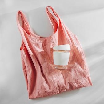 Einkaufstasche aus rosa stoff und wiederverwendbare kaffeetasse. zero waste, plastikfreies konzept.