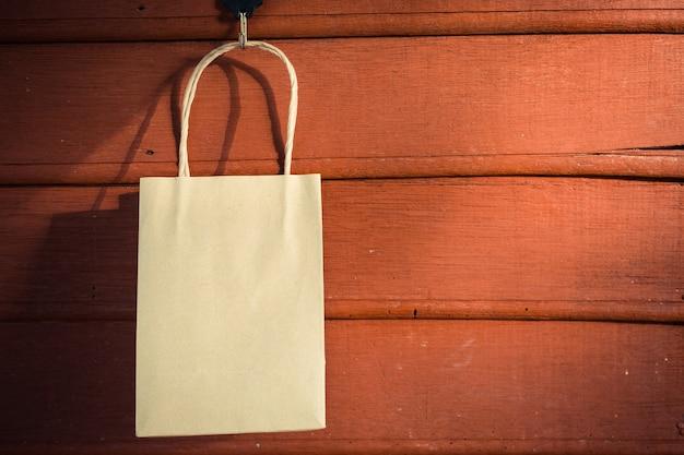Einkaufstasche, die an der hölzernen wand hängt