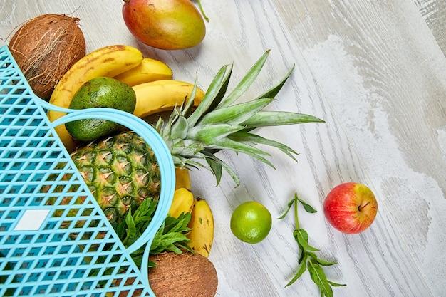 Einkaufstasche für lebensmittel mit exotischen bio-früchten auf weißer oberfläche flache lage verschiedener frischer tropischer früchte, die aus einer wiederverwendbaren einkaufstasche verschüttet werden konzept einer gesunden ernährung und ernährung