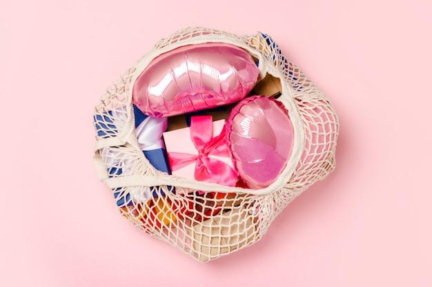 Einkaufstasche mit geschenk und herz formte luftballon auf einer rosa oberfläche. geschenkkonzept für familie, geliebte, weihnachten, valentinstag. . flachgelegt, draufsicht