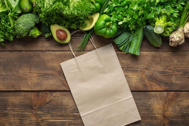Einkaufstasche mit grünem gemüse auf holztisch kaufen sie gesundes essen