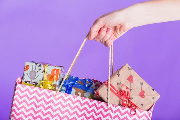 Einkaufstasche mit voll von eingewickeltem geschenk auf purpurrotem hintergrund