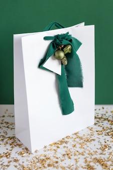 Einkaufstasche mit weihnachtsdekorationen auf tischplatte gegen grünen hintergrund