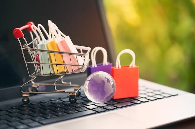 Einkaufstaschen aus papier in einem wagen oder einkaufswagen auf der tastatur. konzept zum online-shopping