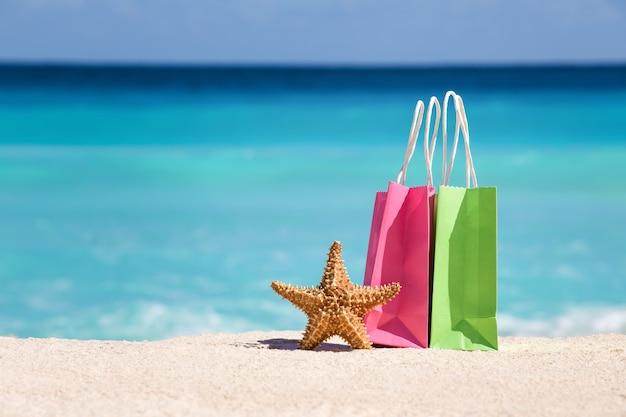 Einkaufstaschen und seesterne auf sand am karibischen meeresstrand