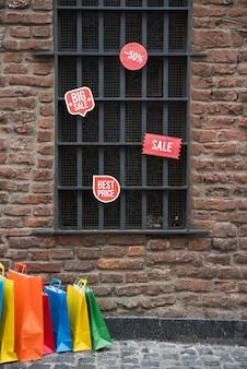 Einkaufstaschen und verkaufstabletten nähern sich fenster auf backsteinmauer