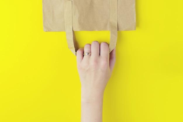 Einkaufstüte auf gelbem hintergrund mit kopienraum. flaches foto einer umgedrehten tasche.