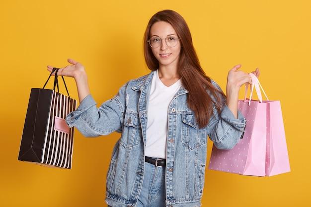 Einkaufsverkauf. erfreute frau mit taschen, steht isoliert über gelber wand