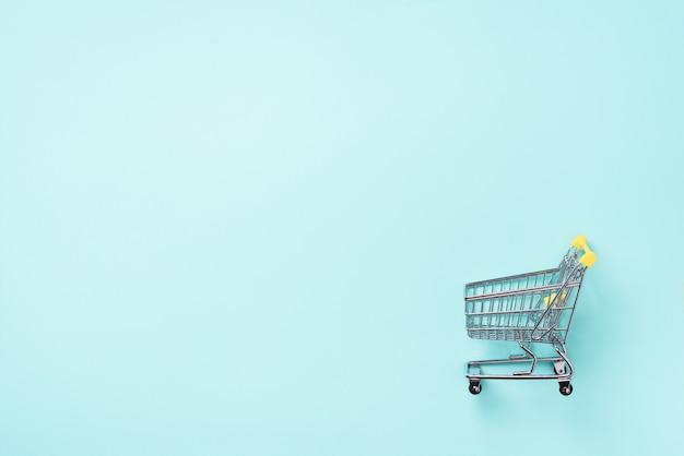 Einkaufswagen auf blauem hintergrund. minimalismus-stil. einkaufswagen im supermarkt.