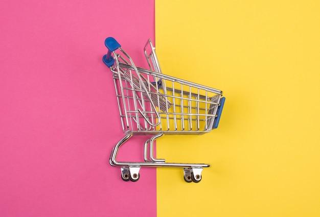 Einkaufswagen auf dem rosa und dem gelb