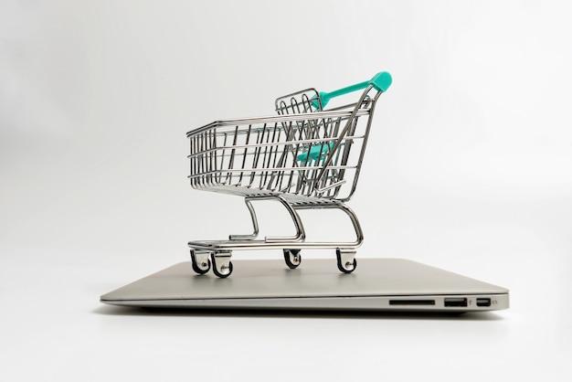 Einkaufswagen auf geschlossenem laptop lokalisiert auf weiß