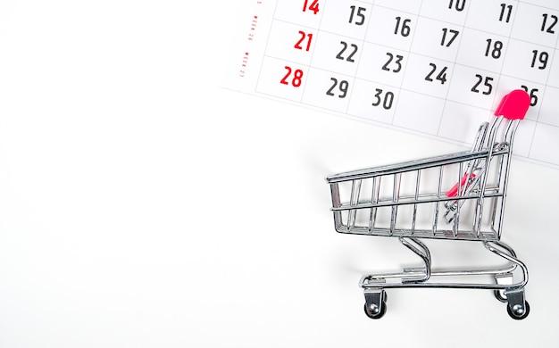 Einkaufswagen auf kalenderhintergrund zeit im kalender zum einkaufen von flatlay