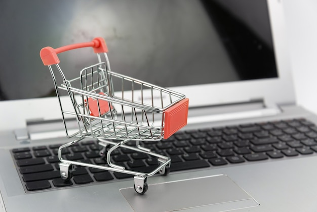 Einkaufswagen auf laptop-hintergrund. einkaufen, investition, kaufkonzept.