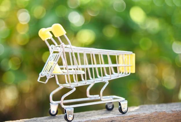 Einkaufswagen auf naturgrün bokeh hintergrund online-shopping black friday-konzept mit gelbem warenkorb