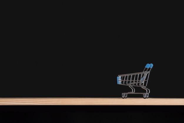 Einkaufswagen auf schwarzer oberfläche. wagen leer auf holztisch