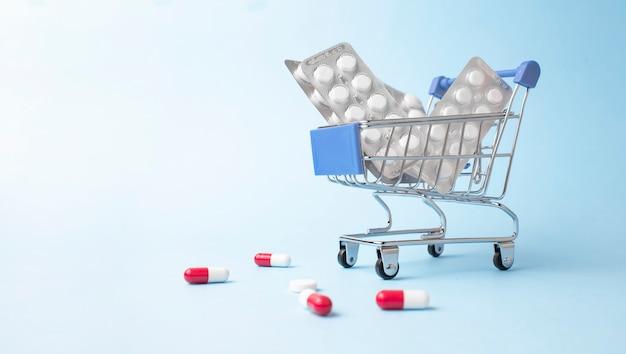 Einkaufswagen aus pillen auf hellblauer oberfläche