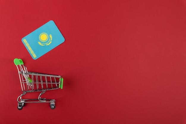 Einkaufswagen des leeren supermarkteinkaufs mini, kasachstan-flagge auf rotem hintergrund