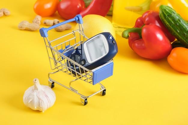 Einkaufswagen, digitales blutzuckermessgerät und gemüse auf gelbem hintergrund. diabetes-diät, diabetischer lebensmittelkorb-kopierraum