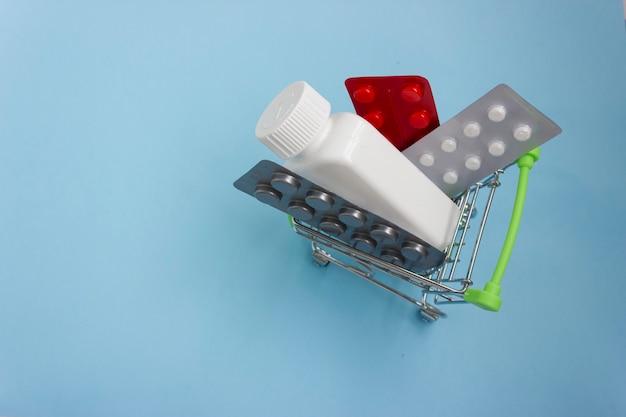 Einkaufswagen geladen mit pillen auf blauem hintergrund. das konzept der medizin und der verkauf und die lieferung von medikamenten. speicherplatz kopieren.