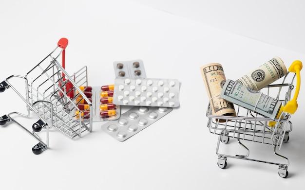 Einkaufswagen mit amerikanischen banknoten, daneben liegt ein einkaufswagen mit tablets.