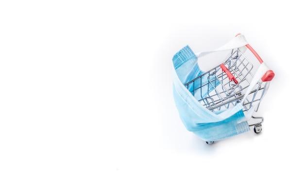Einkaufswagen mit blauer medizinischer schutzmaske gegen coronavirus. sicheres und online-shopping im quarantäne-konzept. heller hintergrund, kopienraum, isolieren.