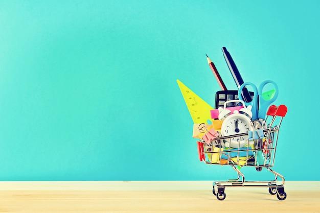 Einkaufswagen mit briefpapiergegenständen. büro- und schulbedarf.