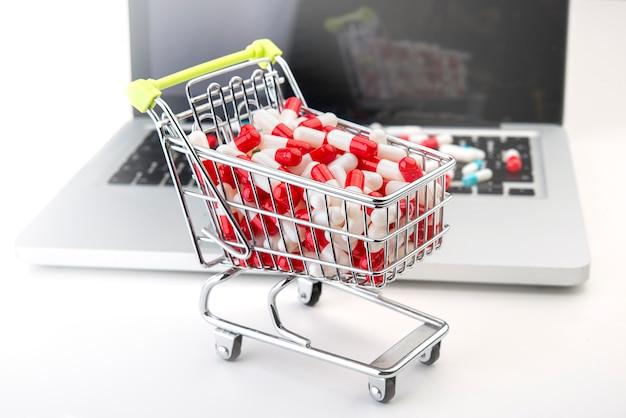 Einkaufswagen mit einem laptop im hintergrund im weißen hintergrund