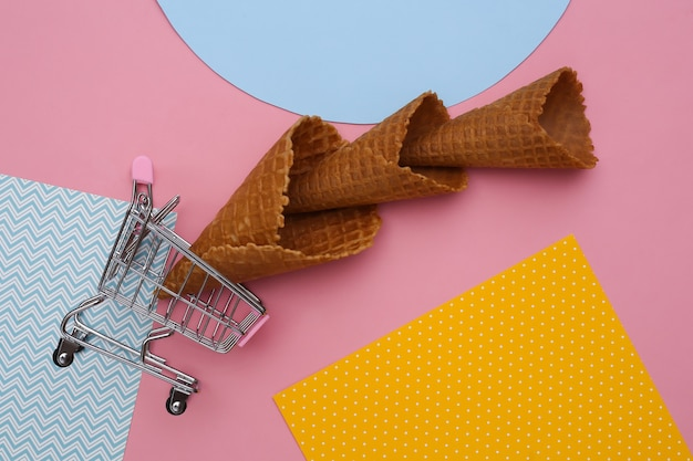 Einkaufswagen mit eiswaffelkegeln auf kreativem buntem papierhintergrund, draufsicht.