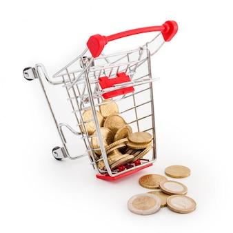 Einkaufswagen mit euro-münzen darin fällt auf weißen hintergrund. konzeptionelle darstellung von versagen, armut und pleite. supermarkt shopping, verkauf und cash back thema. copyspace für text.