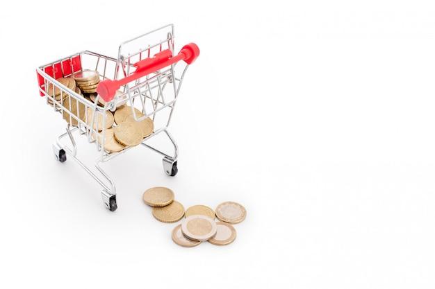 Einkaufswagen mit euro-münzen, die davon auf weißem hintergrund fallen. konzeptionelle darstellung von versagen, armut und pleite. supermarkt shopping, verkauf und cash back thema. copyspace für text.