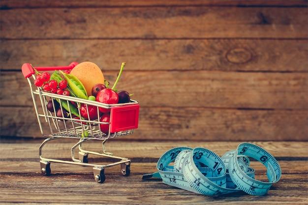 Einkaufswagen mit früchten, beeren und klebebandlinie auf altem holzhintergrund. getöntes bild.