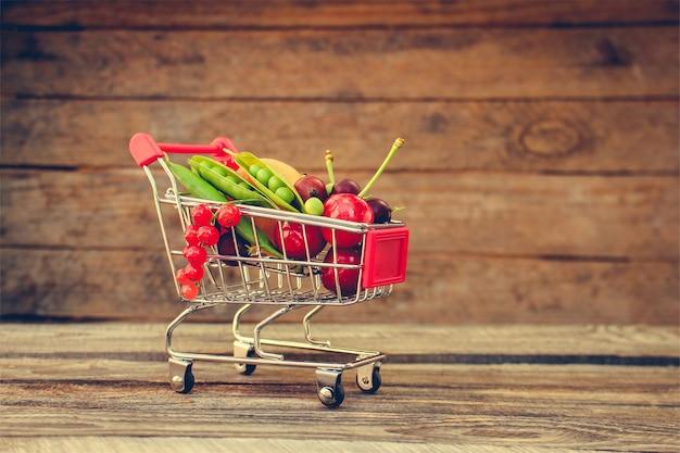 Einkaufswagen mit früchten und beeren auf altem holzhintergrund. getöntes bild.