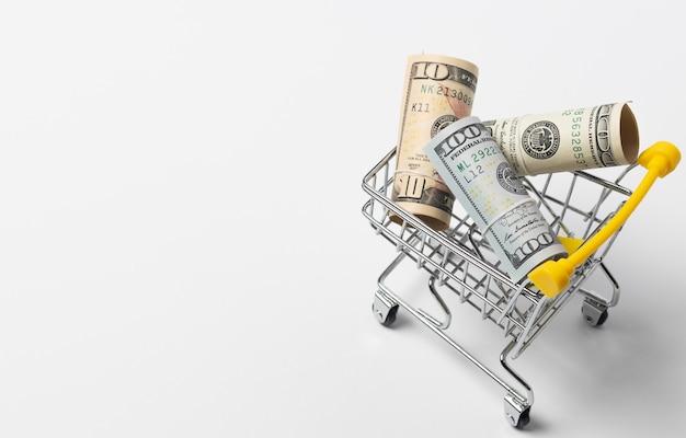 Einkaufswagen mit geld auf weiß, draufsicht