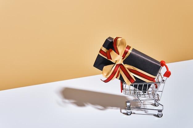 Einkaufswagen mit geschenkbox auf beige grauem hintergrund. geschenke verpackt in kraftpapier schwarz mit band und schleife. feiertags-shopping-konzept.
