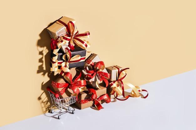 Einkaufswagen mit geschenkboxen auf beige grauem hintergrund. geschenke verpackt in kraftpapier mit band und schleife. feiertags-shopping-konzept.