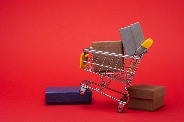 Einkaufswagen mit geschenkboxen auf einem roten.