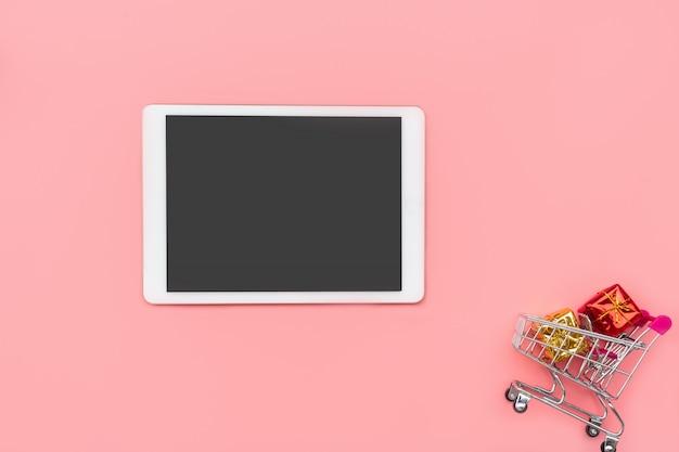 Einkaufswagen mit geschenkboxen und tablette auf rosa hintergrund. einkaufen, online-shopping-konzept, kopierraum, draufsicht