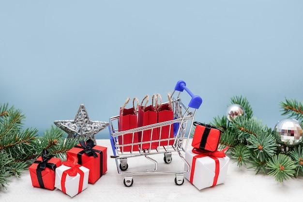 Einkaufswagen mit geschenkboxen und tannenzweigen mit dekoration auf blauem hintergrund. weihnachts- und neujahrsverkauf.