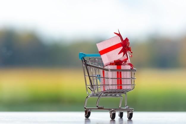 Einkaufswagen mit geschenken auf unscharfem hintergrund, weihnachtseinkaufskonzept