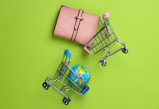 Einkaufswagen mit globus, brieftasche auf grün