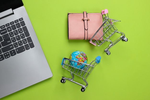 Einkaufswagen mit globus, brieftasche, laptop auf grün