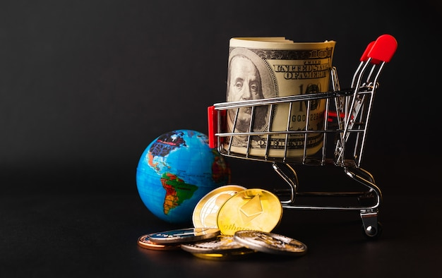 Einkaufswagen mit goldenen münzen, winzigem globus und 100 dollar im einkaufswagen