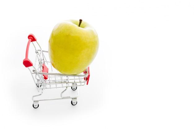 Einkaufswagen mit großem grünem apfel auf weiß. obst im supermarkt kaufen. selbstbedienungs-supermarkt voller einkaufswagen. verkauf, überfluss, erntethema. copyspace für text.