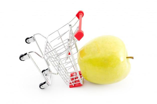 Einkaufswagen mit großem grünem apfel auf weiß. obst im supermarkt kaufen. selbstbedienungs-supermarkt voller einkaufswagen. verkauf, überfluss, erntethema