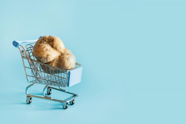 Einkaufswagen mit hässlicher kartoffel.