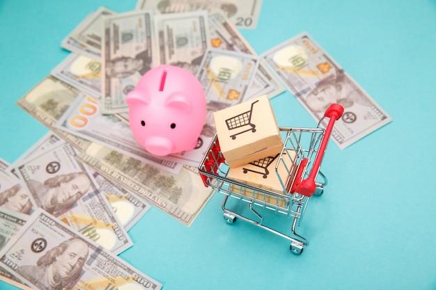 Einkaufswagen mit kisten, rosa sparschwein und dollarbanknoten auf blau.