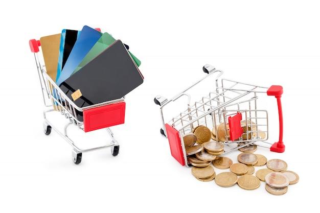 Einkaufswagen mit kreditkarten und einem anderen wagen voller euro-münzen, die auf weißem hintergrund davon fallen. kreditkarten gewinnen und bargeld wird besiegt. alte und neue zahlungsmethoden.