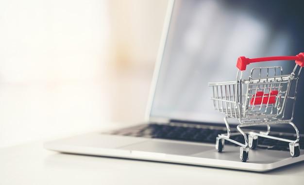 Einkaufswagen mit laptop auf dem schreibtisch